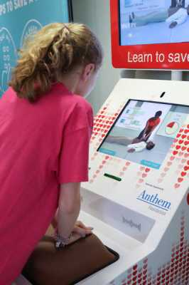 Young girl learning Hands-Only CPR at the American Heart Association Hands-Only CPR training kiosk at Cincinnati-Northern Kentucky International Airport. copyright American Heart Association 2017 Photos by Tommy Campbell Photography